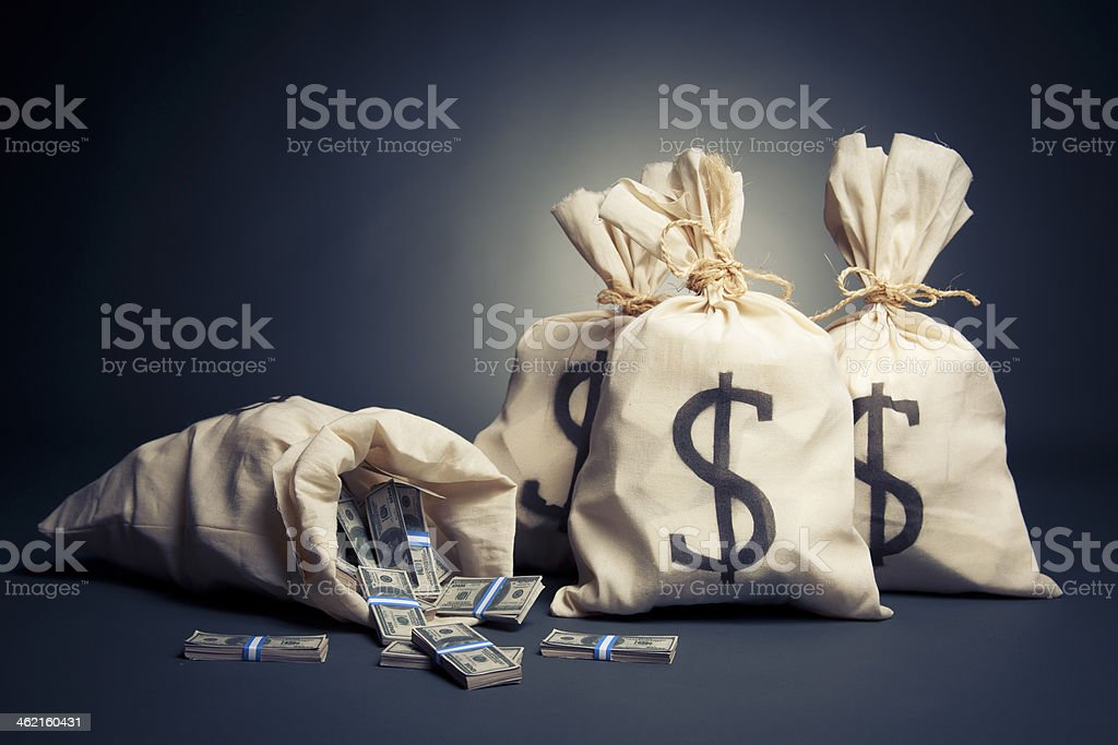 White bags with dollar signs on them filled with money stock photo