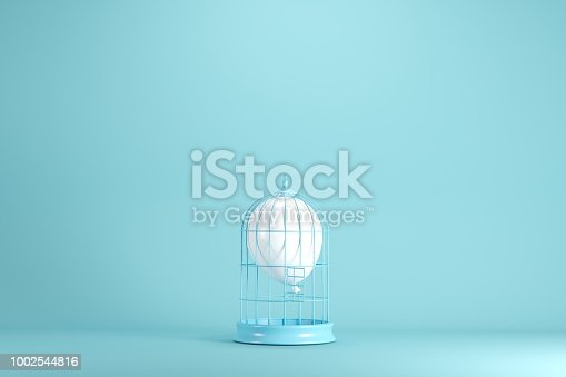 903520476 istock photo White balloon floating in white cage on blue background. minimal idea concept. 1002544816