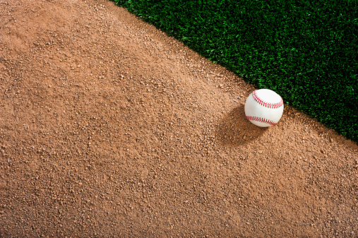White baseball on a dirt track next to the grass