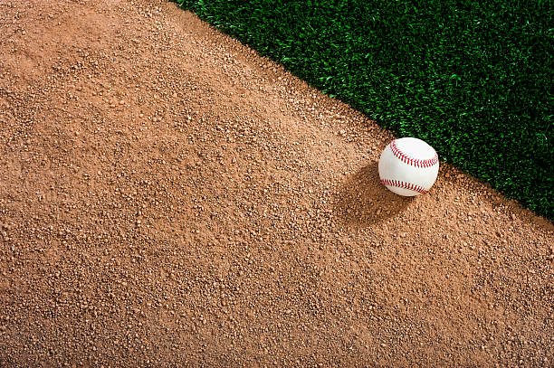 White baseball on a dirt track next to the grass Looking down on a Baseball in the dirt next to grass. baseball diamond stock pictures, royalty-free photos & images