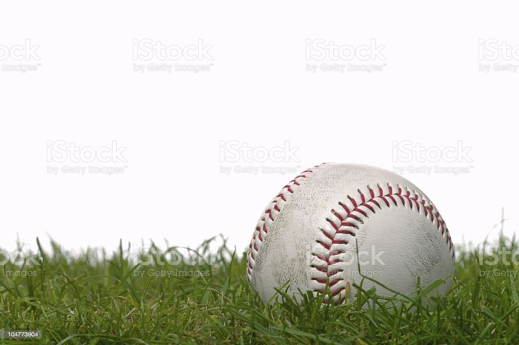 A white baseball with red stitching resting on grass stock photo