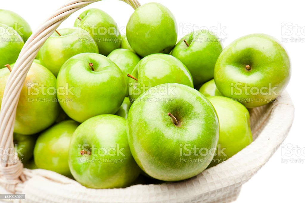 White basket full of green apples on white background stock photo