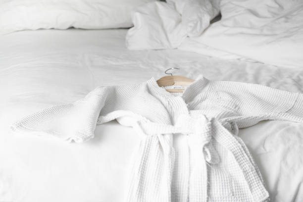 white bath robe on the bed in hotel room stock photo