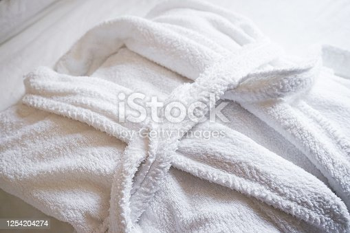 The concept of rest in a hotel. White Bathrobe on bed in bedroom close-up.