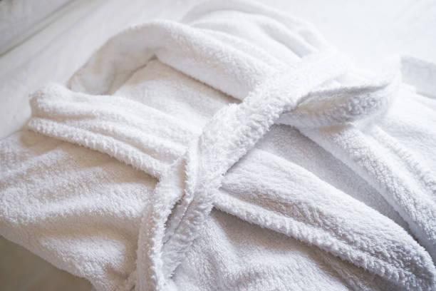 accappatoio bianco sul letto in camera da letto, primo piano. il concetto di riposo in un hotel. - accappatoio foto e immagini stock