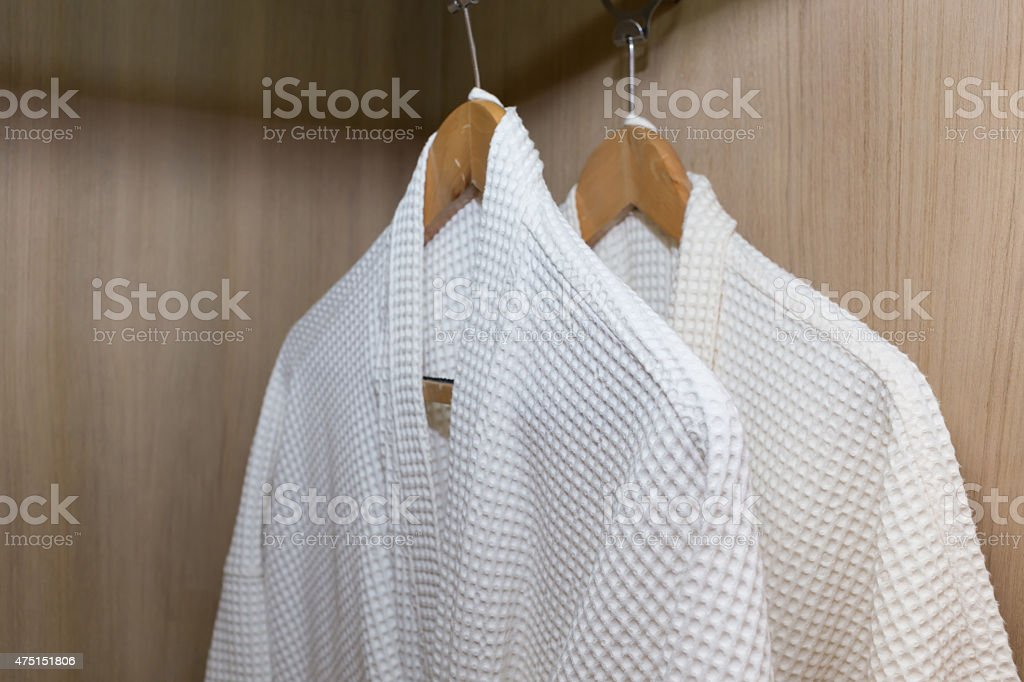 white bathrobes hanging in wooden closet stock photo