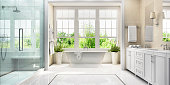 Large white bathroom with bath, large window, shower and two washbasins