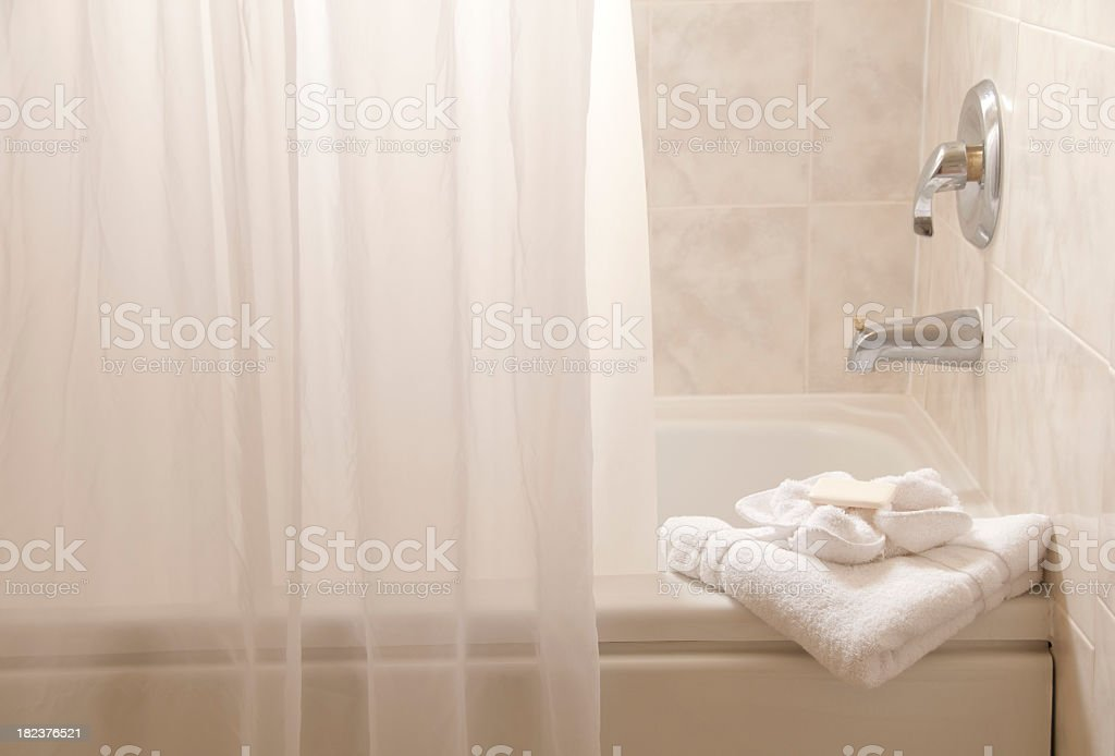 White bathroom with bathtub, towels and a shower curtain stock photo