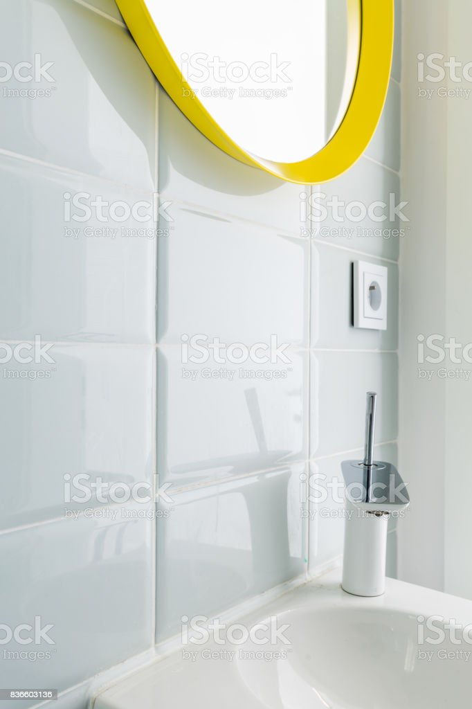 White bathroom with yellow mirror stock photo