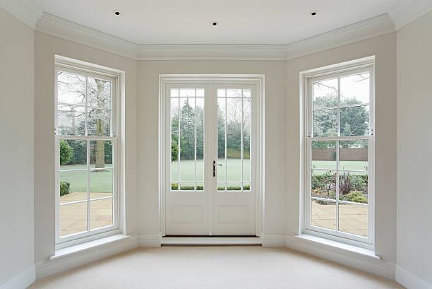 white bay windows and French doors stock photo