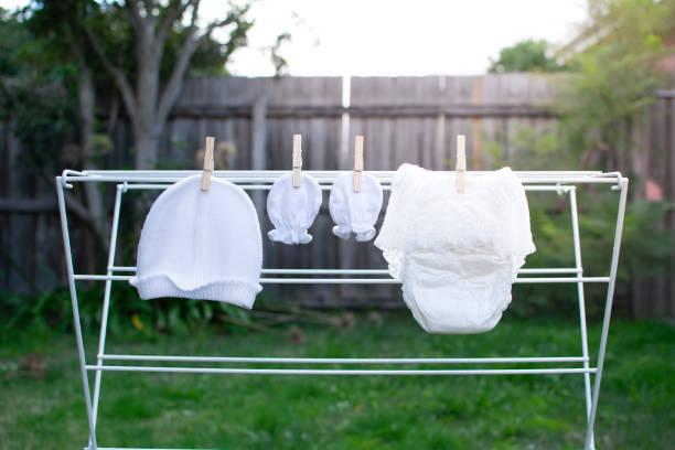 weiße mütze, handschuhe und windel hängenden bereit für neues baby geboren - windel partys stock-fotos und bilder