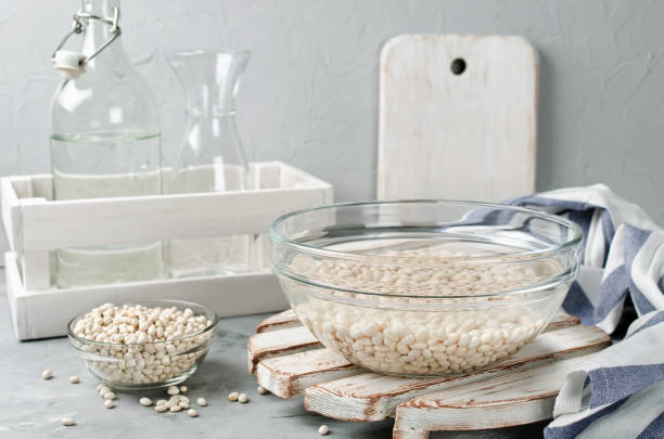 white beans soaked in water in a glass bowl - drenched stock pictures, royalty-free photos & images
