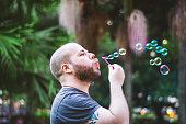 White bearded man playing with bubbles