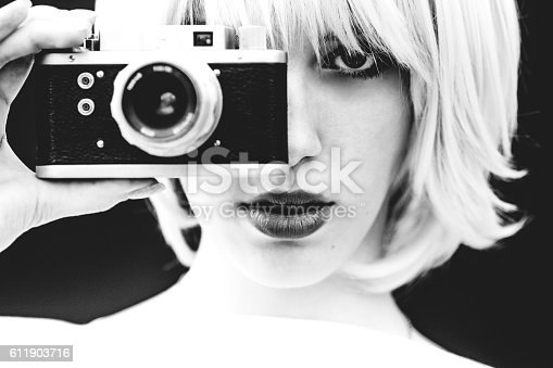 Beautiful girl filming with analog camera