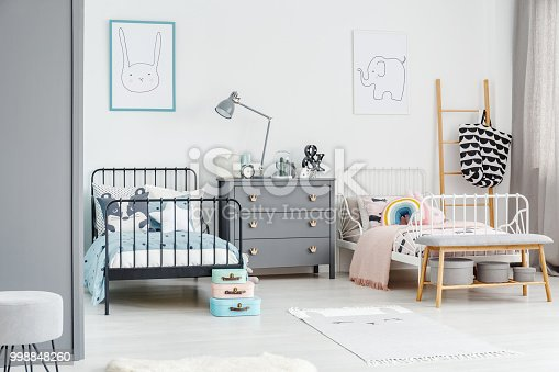 istock White bed for a girl and black one for a boy in a siblings bedroom interior with posters of a rabbit and an elephant on a white wall. Simple scandi design. Real photo 998848260