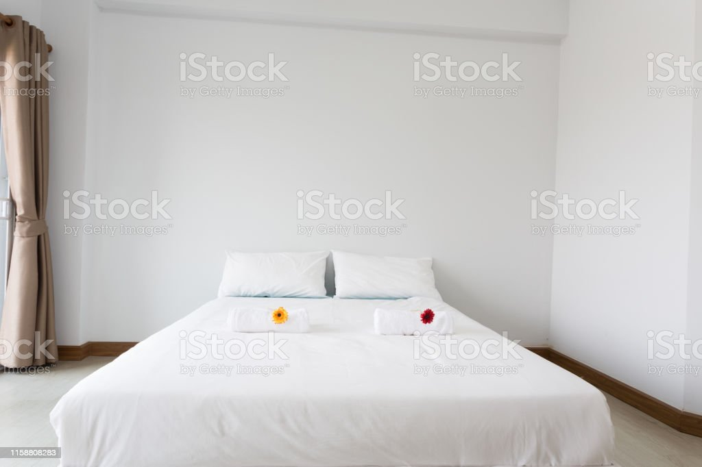 White bed in the white room with clear light from left side