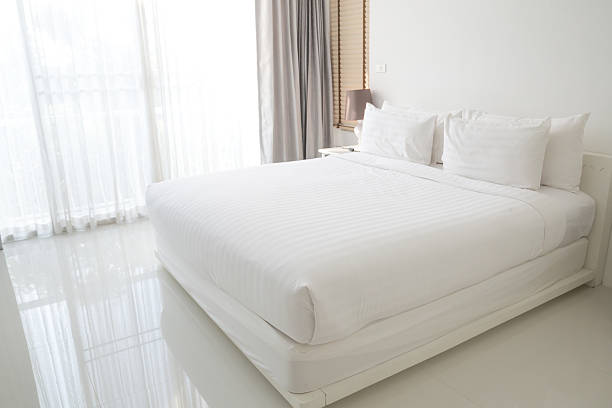 White bed sheets and pillows stock photo