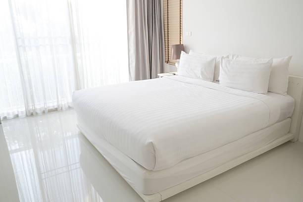 folhas e almofadas cama branca - sheet imagens e fotografias de stock