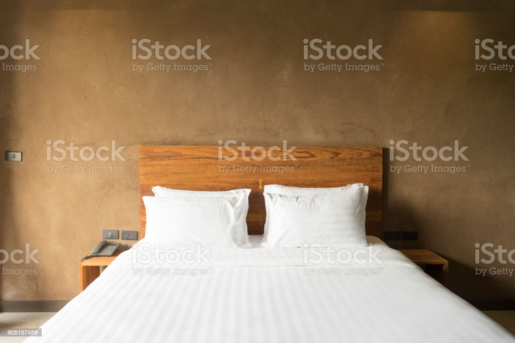 white bedding and pillow in hotel room, two pillows in hotel.