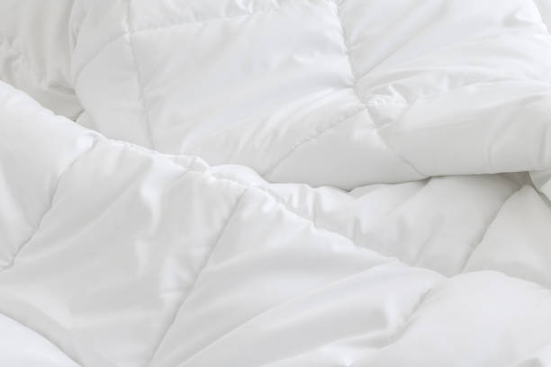 White bedding sheets background. Messy bed concept. White bedding sheets background. Messy bed concept. duvet stock pictures, royalty-free photos & images