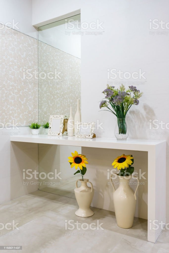 White bedroom interior with a wooden makeup table, a pouffe, a mirror...