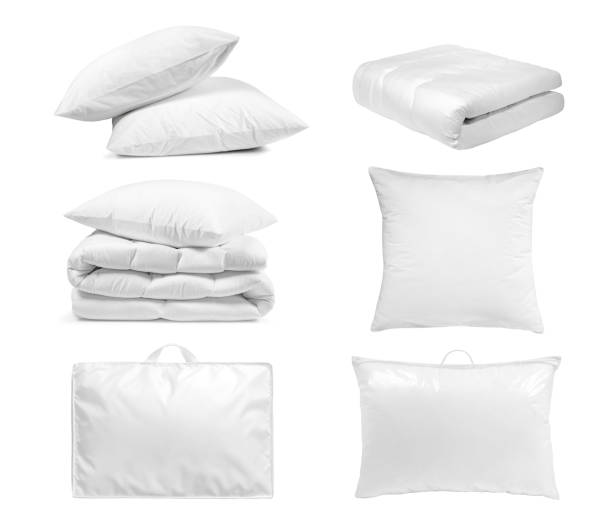 White bedroom textile items set isolated. White bedroom textile items set isolated. Pillows and duvet- laying, folded, stacked and packed against the white background. duvet stock pictures, royalty-free photos & images