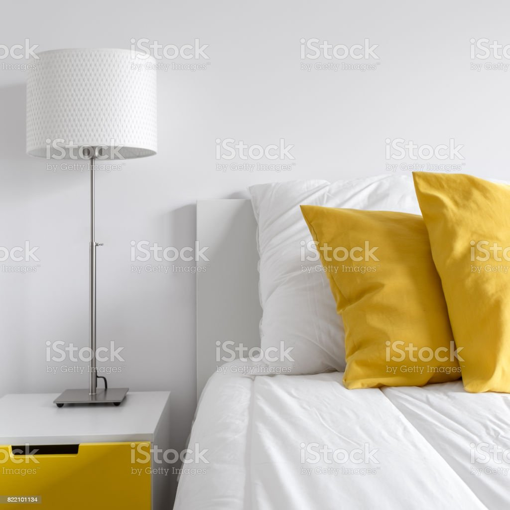 White bedroom with yellow sidetable stock photo