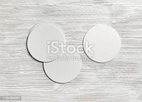 Blank white beer coasters on light wood table background. Flat lay.