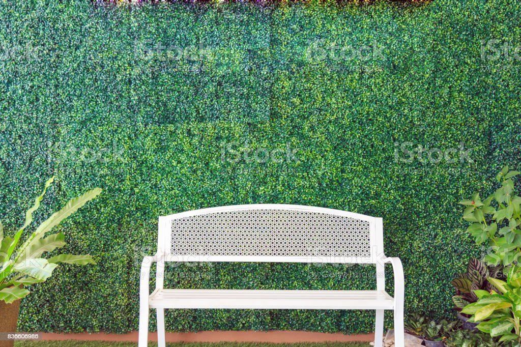 A white bench on artificial grass and ornamental plants on artificial plants wall. stock photo