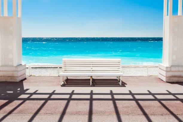 white bench on the promenade des anglais in nice, france - nizza sehenswürdigkeiten stock-fotos und bilder