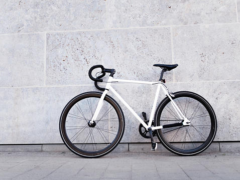 White bicycle leaning against light grey wall