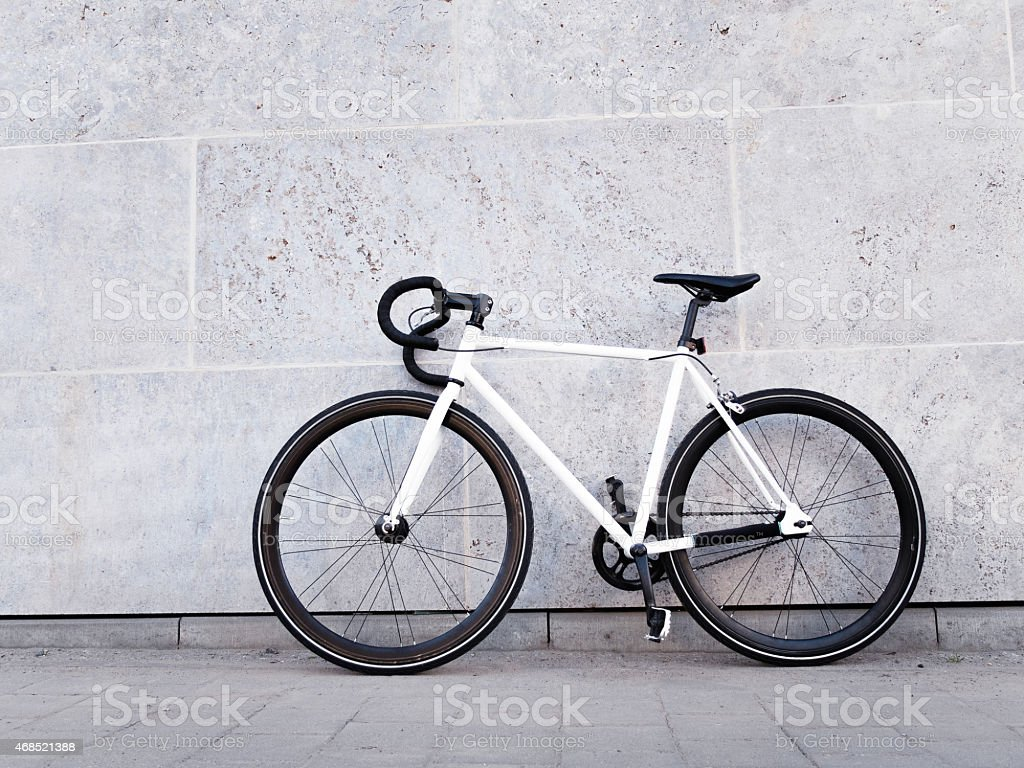 White bicycle leaning against light grey wall stock photo