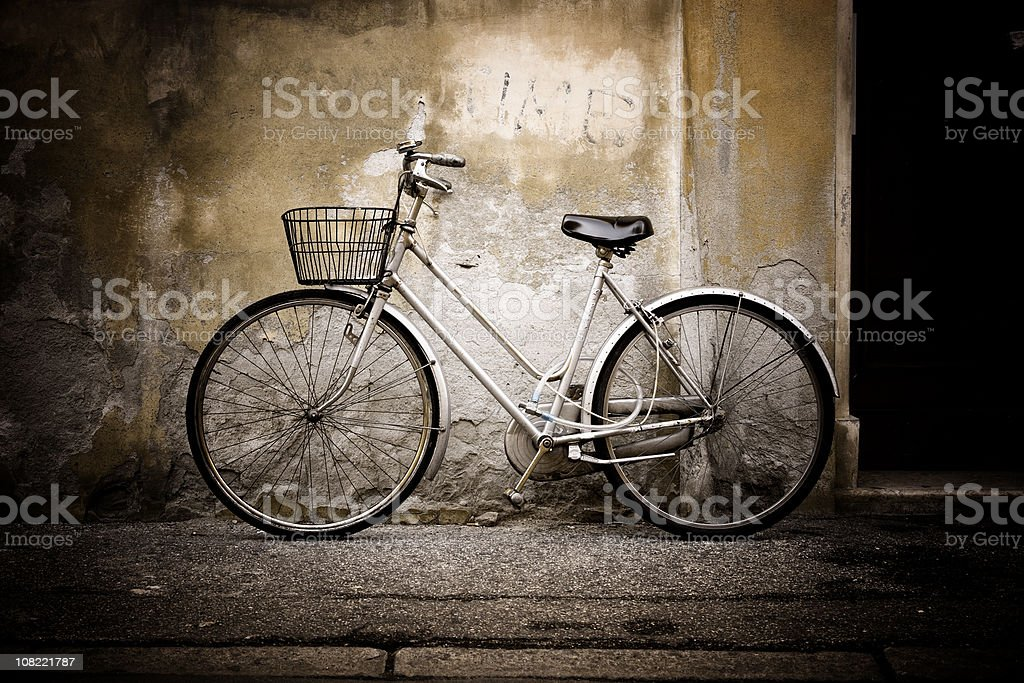 White bicycle leaning aginst cement wall of building royalty-free stock photo