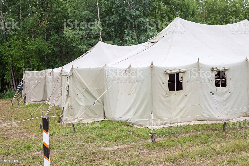 white big army tent in field stock photo