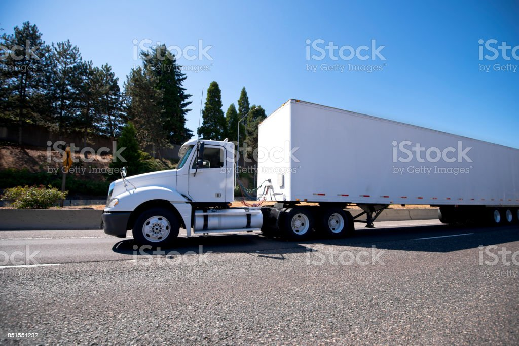 White big rig day cab semi truck and dry van trailer for local delivery and reposition of industrial cargo stock photo
