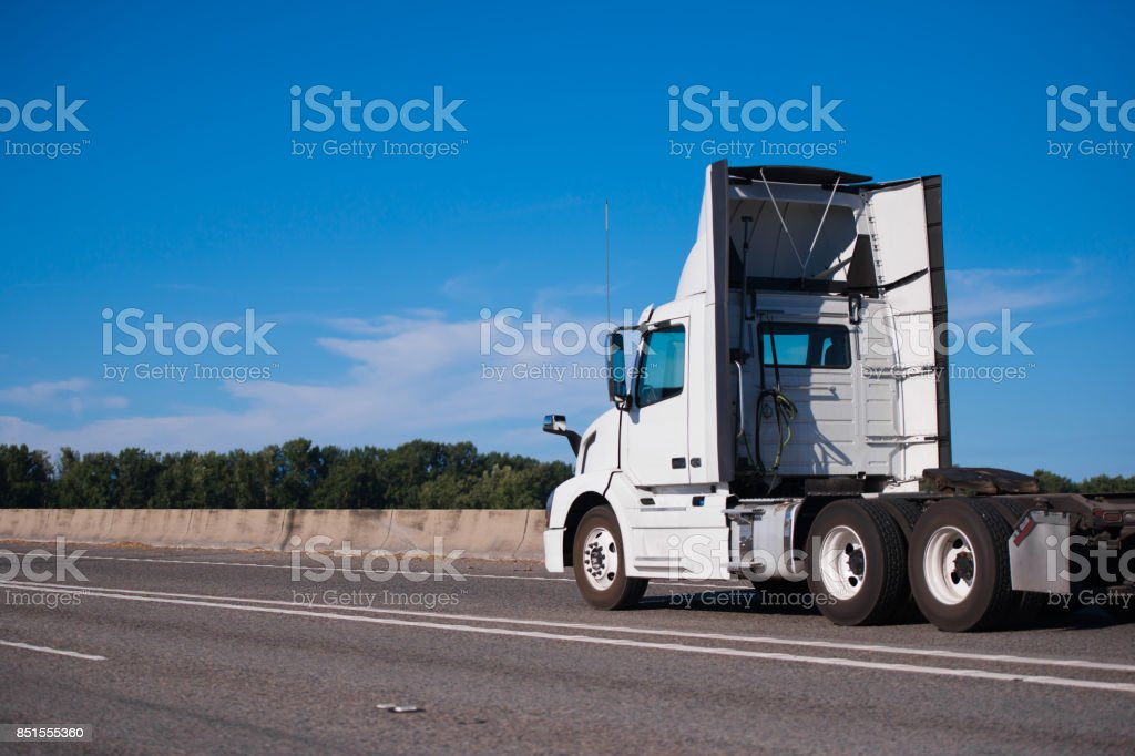 White big rig day cab semi truck with spoilers run on wide interstate highway to warehouse for pick up semi trailer stock photo