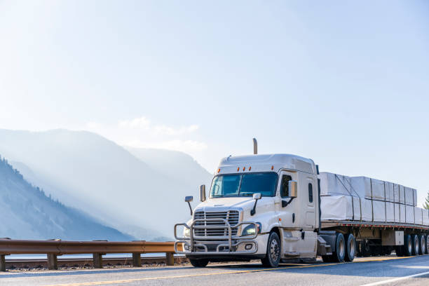 White big rig semi truck tractor transporting stocked lumber on the flat bed semi trailer and driving in Columbia River Gorge stock photo