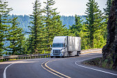 Big rig white powerful American bonnet long haul semi truck transporting commercial cargo in refrigerated semi trailer moving uphill on winding road with a green trees and safety fence on the side