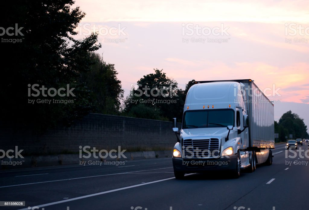 White big rig semi truck with dry van trailer driving on evening road with headlight and sunset sky stock photo