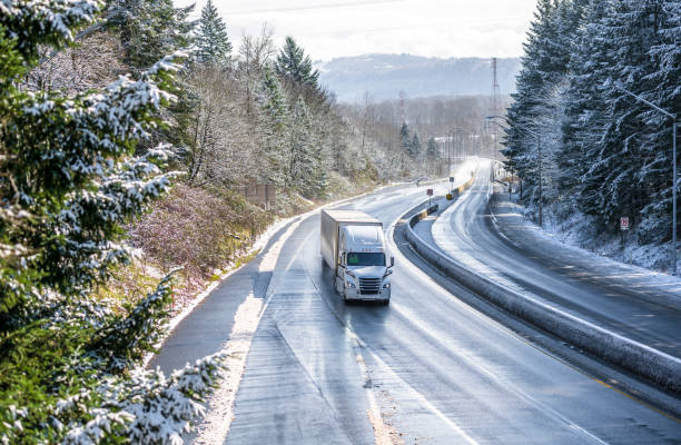 White big rig semi truck with semi trailer going on the wet winter road with snow trees on the side stock photo
