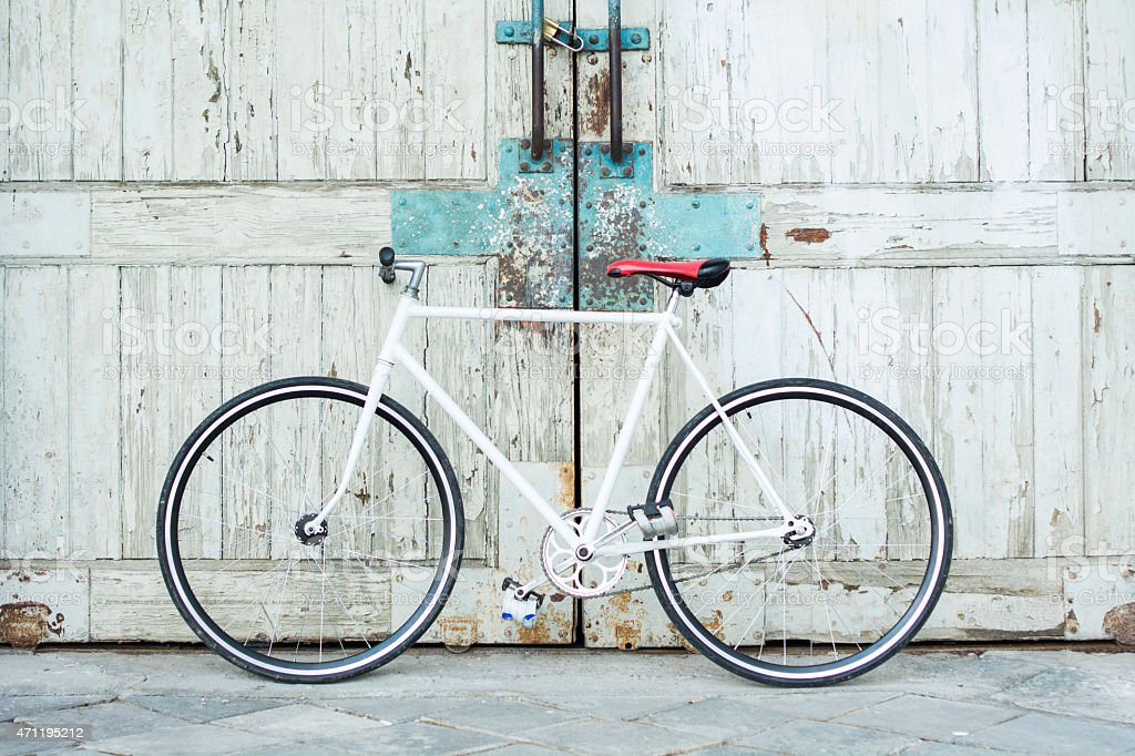 White bike leaning against dingy wooden gate doors stock photo