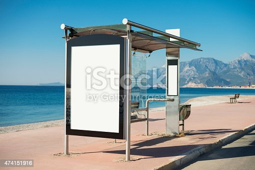White billboard (Clipping Path ) on a bus station on the beach. Image taken on a bright sunny morning in Antalya, Turkey. Focus on the billboard, Camera Nikon D800