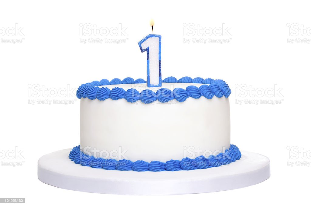 White birthday cake with blue piping with a 1 candle on top stock photo