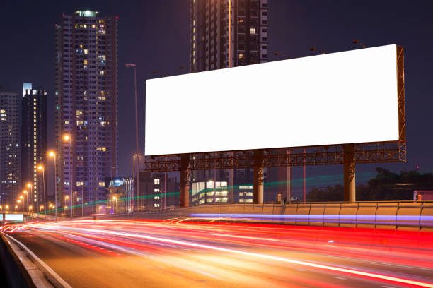 white blank billboard on light trails, street, city and urban in the dusk or night- can advertisement for display or montage product or business. - billboard stock photos and pictures