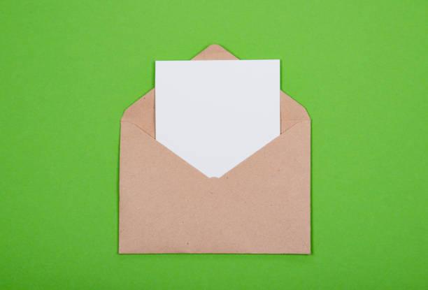 Weiße leere Karte in geöffneten Handwerk Umschlag auf grünem Hintergrund mit Textfreiraum. – Foto