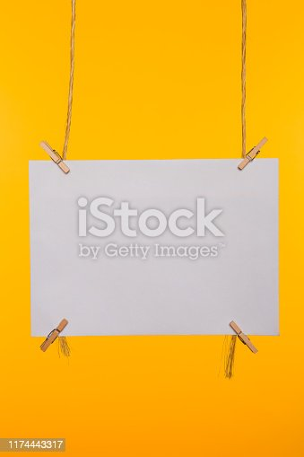 818681972istockphoto White blank card pinned with clothes pegs on a yellow background 1174443317