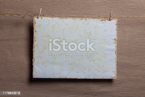 818681972istockphoto White blank card pinned with clothes pegs on brown paper background 1179843518