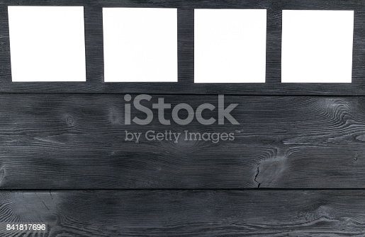 818681972istockphoto White blank cards on black wooden table with copy space. Creative reminder, small sheets of paper on desk with empty space for text, light memo background 841817696