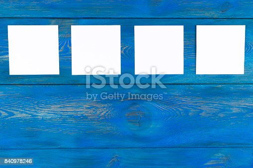 818681972istockphoto White blank cards on blue wooden table with copy space. Creative reminder, small sheets of paper on desk with empty space for text, light memo background, 840978246
