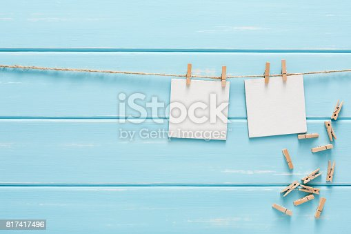 818681972istockphoto White blank cards on rope, blue wooden background 817417496